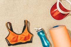 o plano coloca com arranjo do tampão, do sportswear fêmea, da esteira e da garrafa de água imagens de stock