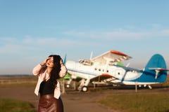 O plano da menina que levantam perto dos aviões, da mulher do viajante e a trouxa consideram o avião na janela de vidro do aeropo fotografia de stock royalty free