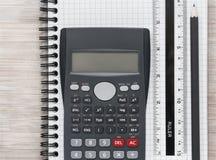 O plano da mesa coloca com calculadora, régua e lápis em um caderno imagem de stock