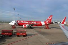 O plano de Air Asia tailandês, Airbus A320 é estacionado no parque de estacionamento e contra a escadaria do embarque do passagei Imagens de Stock Royalty Free