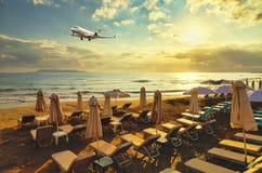O plano de assunto privado na aterrissagem voa sobre o Sandy Beach com os vadios do sol no fundo do por do sol, do sol e das nuve imagem de stock