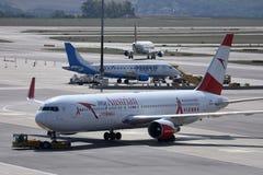 O plano de Austrian Airlines que taxiing na pista de decolagem no aeroporto de Viena, VIE imagem de stock