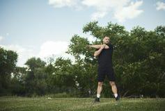 O plano distante do homem atrativo que faz o esticão entrega exercícios, no parque imagens de stock