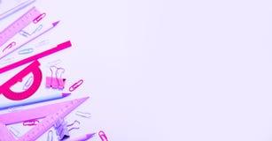 O plano do statinery da escola coloca no fundo cor-de-rosa imagem de stock