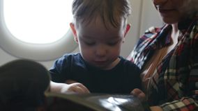 O plano está voando, a criança está sentando-se na mamã nas penas, compartimento do ` s das crianças do lookin com imagens vídeos de arquivo