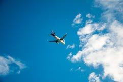 o plano está voando para nublar-se o céu azul do ariport entre o sunlig Imagem de Stock Royalty Free