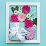 O plano floral coloca o conceito mínimo com presente belamente envolvido Dia feliz do `s da matriz Fotos de Stock Royalty Free