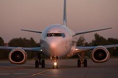 O plano na pista de decolagem na noite no por do sol Fotografia de Stock Royalty Free