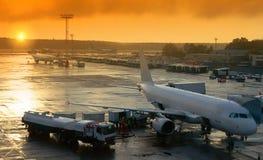 O plano no aeroporto está preparando-se para decolar é de abastecimento e de carregamento a bagagem fotografia de stock