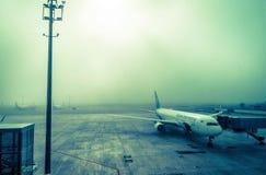 O plano no aeroporto na névoa Foto de Stock