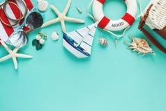 O plano tropico coloca com chapéu de palha, saco, estrela do mar, escudos, óculos de sol, barco, brincos no fundo verde A forma d fotografia de stock