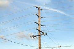 O pólo de potência de madeira com alta tensão assina o céu azul Imagens de Stock Royalty Free