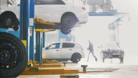 O pneu na frente de uma estação do serviço com os carros no elevador vídeos de arquivo