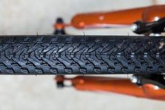 O pneu nodoso do Mountain bike do passo fecha-se acima na bicicleta alaranjada imagem de stock