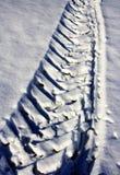 O pneu segue o branco da neve do inverno do passo do trator Imagens de Stock