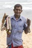 O pobre homem vende a joia aos turistas na praia branca da areia Sri Lanka Imagem de Stock Royalty Free