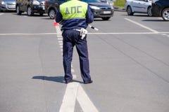 O polícia de tráfego trabalha em uma rua no tempo do dia Imagens de Stock Royalty Free