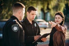 O polícia escreve o testemunho do motorista fêmea fotografia de stock royalty free