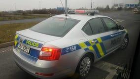 O polícia senta-se no carro na estrada e na movimentação video estoque