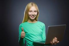 O polegar feliz bem sucedido da mostra da menina do retrato do close up ascendente e que usa o portátil isolou o fundo cinzento Fotos de Stock