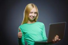 O polegar feliz bem sucedido da mostra da menina do retrato do close up ascendente e que usa o portátil isolou o fundo cinzento Imagem de Stock Royalty Free
