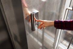 O polegar pressiona o botão do elevador, uma mão que alcança para o botão, o elevador de espera da menina, começo da tecla Imagem de Stock