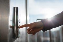 O polegar pressiona o botão do elevador, uma mão que alcança para o botão, o elevador de espera da menina, começo da tecla Foto de Stock
