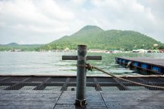 O polo de aço da doca tem a corda amarrada lhe com lago e montanha seja Fotografia de Stock