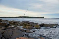 O polo de pesca está em uma costa rochosa Fotografia de Stock Royalty Free