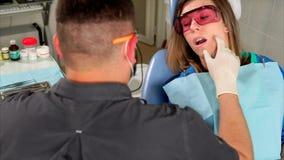 O polyclinic do dentista do doutor sonda o mordente do ` s da mulher para verificar a anestesia dos dentes video estoque