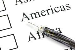 O ponto do lápis à caixa de seleção em Americas text. Imagens de Stock Royalty Free