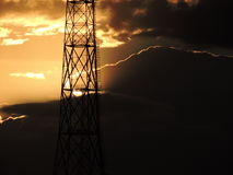 O por do sol é magnífico atrás da torre de comunicação foto de stock
