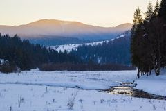 O por do sol alaranjado brilhante em montanhas azuis do inverno ajardina Imagens de Stock Royalty Free