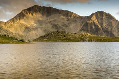 O por do sol amarelo sobre o lago Tevno e Kamenitsa repicam, montanha de Pirin foto de stock royalty free