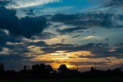 O por do sol atrás dos campos e das árvores de almofada Foto de Stock