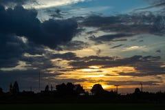 O por do sol atrás dos campos e das árvores de almofada Fotos de Stock