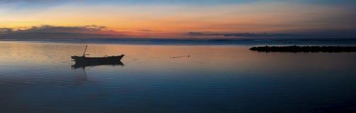 O por do sol com barco do fisher e ainda molha em Gili Air Island, Indo Fotos de Stock
