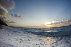 O por do sol da ilha de Lefkada pelas nuvens de ondas do mar ajardina fotografia de stock
