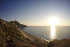 O por do sol da ilha de Lefkada pelas nuvens de ondas do mar ajardina a praia fotografia de stock royalty free