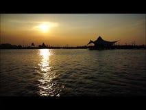 O por do sol em uma praia capturou com céu alaranjado e reflexão na água video estoque
