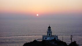 O por do sol do farol em Santorini, Grécia fotos de stock