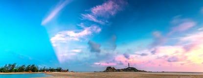 O por do sol do farol do KE GA com os recifes mais lisos patted ressaca cria nuvens no mar Foto de Stock