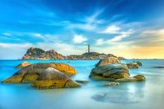 O por do sol do farol do KE GA com os recifes mais lisos patted ressaca cria nuvens no mar Fotos de Stock