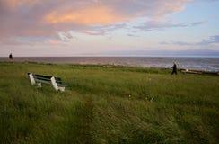 O por do sol ilumina as nuvens de tempestade sobre Juan de Fuca Strait quando os povos andarem no parque imagem de stock royalty free