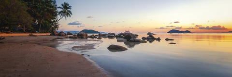 O por do sol do mar balança a praia no fundo do céu azul Nascer do sol da noite da beleza Praia de Sandy com rochas fotografia de stock royalty free