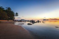 O por do sol do mar balança a praia no fundo do céu azul Nascer do sol da noite da beleza Praia de Sandy com rochas imagens de stock royalty free