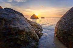 O por do sol do mar balança a praia no fundo do céu azul Nascer do sol da noite da beleza Fundo para um cartão do convite ou umas foto de stock