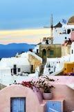 O por do sol na cidade e nos turistas de Oia que apreciam suas férias Fotografia de Stock Royalty Free