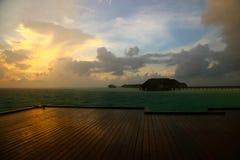 O por do sol na ilha de Maldivas, casas de campo da água recorre imagens de stock royalty free
