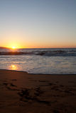 O por do sol na praia com pé imprime na areia Imagens de Stock Royalty Free